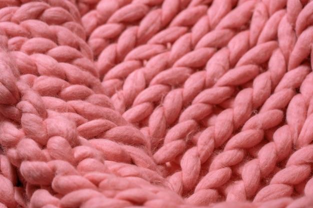 Handgemachte gestrickte große decke aus merinowolle, super dickes garn, trendiges konzept. nahaufnahme der gestrickten decke, merinowollehintergrund. designerdecke aus rosafarbener korallenrauchwolle