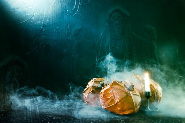 Handgemachte halloween-kürbise mit brennender kerze und geist und rauch
