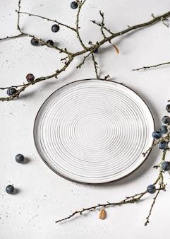 Handgemachte keramikplatte mit schwarzdornzweigen auf weiß