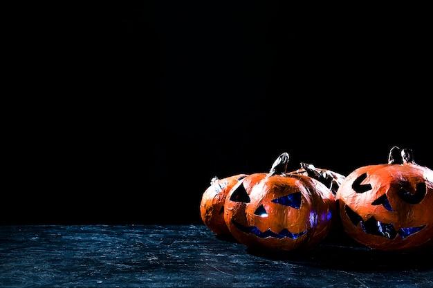 Handgemachte kürbise in der halloween-art belichteten das innere, das auf seite in der dunkelheit liegt