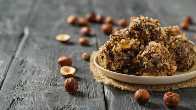 Handgemachte kugeln aus getrockneten früchten, nüssen und schokolade auf einem holztisch. leckere frische hausgemachte süßigkeiten.