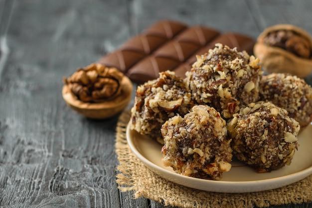 Handgemachte kugeln aus getrockneten früchten, nüssen und schokolade auf einem holztisch.