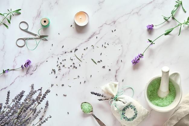Handgemachte lavendelbeutel und hausgemachtes badesalz. lavendelblüten, frisch und trocken. flach lag auf hellem marmor