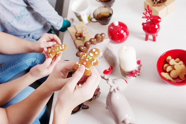 Handgemachte lebkuchenplätzchen für weihnachten in den kinderhänden.