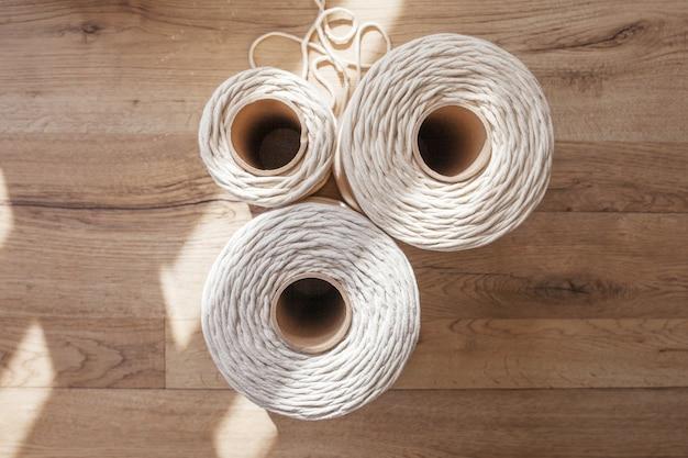 Handgemachte makramee flechten und baumwollfäden auf rustikalem holztisch. hobby strick baumwollfadenrolle auf einem holzbrett. weibliches hobby. top vew