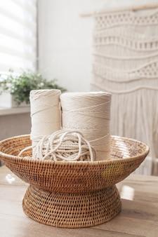 Handgemachte makramee flechten und baumwollfäden auf rustikalem holztisch. hobby strick baumwollgarnrolle in gewebtem korb auf einem holzbrett.