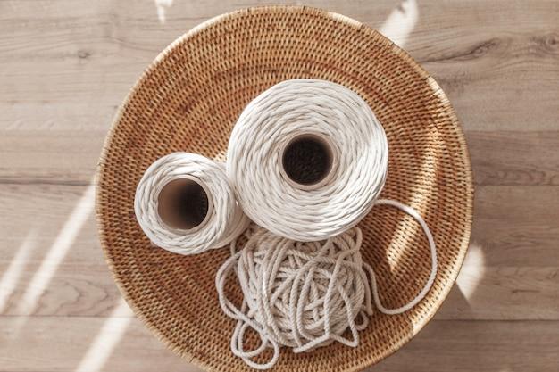 Handgemachte makramee flechten und baumwollfäden auf rustikalem holztisch. hobby stricken baumwolle draufsicht des fadens im gewebten korb auf einem holzbrett.