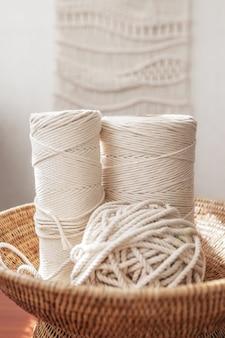 Handgemachte makramee flechten und baumwollfäden auf rustikalem holztisch. hobby stricken baumwollfaden in gewebtem korb auf einem holzbrett. weibliches hobby