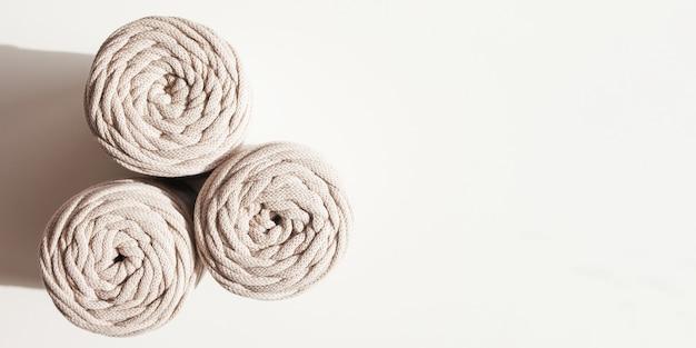 Handgemachte makramee-geflecht und baumwollfäden auf weißem hintergrund. hobby-strickgarnrolle aus baumwolle. natürliche baumwollkordel. weibliches hobby. platz kopieren. banner