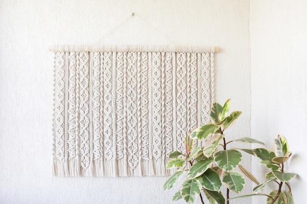 Handgemachte makramee. wanddekoration aus 100% baumwolle mit holzstab an einer weißen wand. weibliches hobby. eco-freundliches modernes strick-diy-naturdekorationskonzept im innenraum