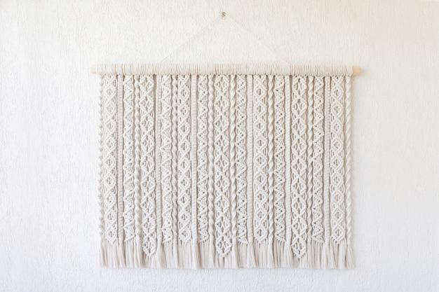 Handgemachte makramee. wanddekoration aus 100% baumwolle mit holzstab an einer weißen wand. weibliches hobby. eco freundliches modernes stricken diy natürliches dekorationskonzept im innenraum