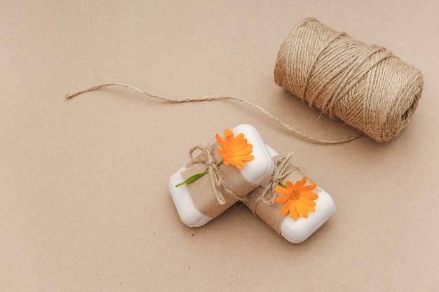 Handgemachte naturseife, verziert mit kraftpapier, orangefarbenen ringelblumen, garn und schere