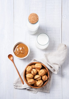 Handgemachte nüsse mit gekochter milch und karamell in einer schüssel und einem glas milch auf einem weißen holztisch gebacken. draufsicht und flach liegen