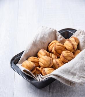 Handgemachte nüsse mit karamell in einer auflaufform auf einem weißen tisch gebacken. speicherplatz kopieren