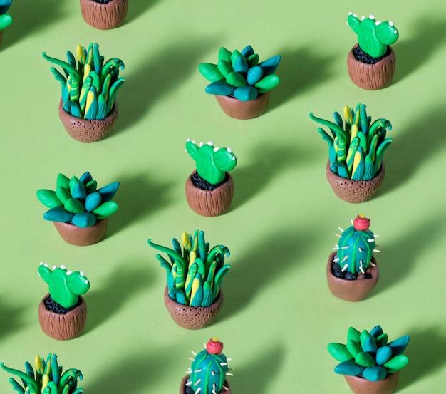 Handgemachte plastikgrüne kakteen und sukkulenten in töpfen. kreatives muster mit tonfiguren von kakteen.