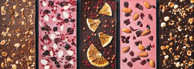 Handgemachte schokoriegel mit einer vielzahl von getrockneten früchten und nussbelägen.