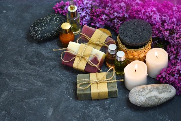 Handgemachte seife, aromakerzen, lila blumen, aromatische öle und steine im dunkeln.