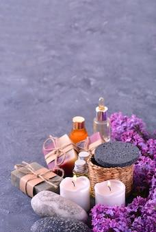 Handgemachte seife, aromakerzen, lila blumen, aromatische öle und steine