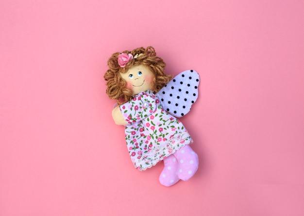 Handgemachte tilda engel aus stoff auf rosa.