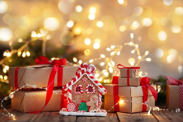 Handgemachte weihnachtsgeschenkbox mit lebkuchenhaus unter einem weihnachtsbaum mit defokussierten lichtern.
