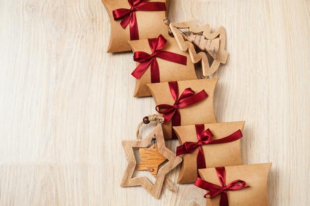 Handgemachte weihnachtsgeschenke aus kraftpapier und holzspielzeug am weihnachtsbaum