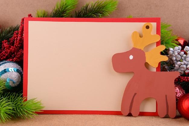 Handgemachte weihnachtskarte mit weihnachtsschmuck auf holzoberfläche