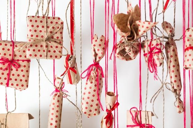 Handgemachter adventskalender, der an einer weißen wand hängt. geschenke in kraftpapier eingewickelt und mit roten fäden und bändern gebunden.