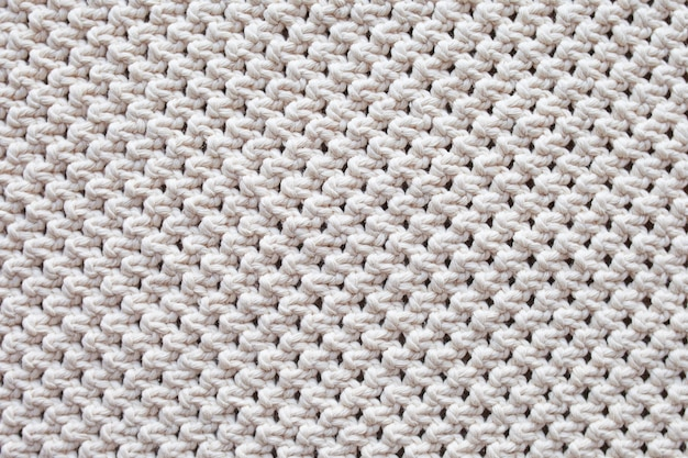 Handgemachter beiger makramee-musterhintergrund. makramee-textur, eco-freundlich, modernes stricken.