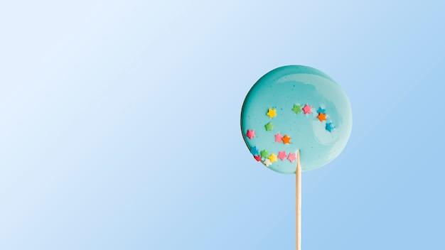 Handgemachter blauer lutscher auf holzstab auf blauem hintergrund. das konzept der süßigkeiten für die feiertage, geburtstag. schokoriegel
