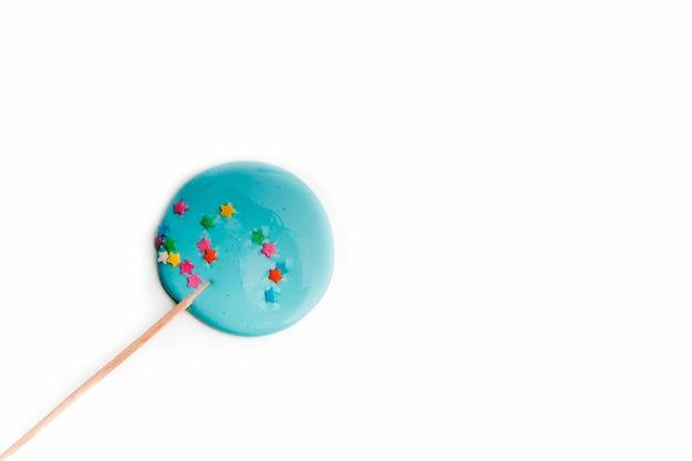 Handgemachter blauer lutscher auf holzstab auf weißem hintergrund. das konzept der süßigkeiten für die feiertage, geburtstag. schokoriegel. flach liegen
