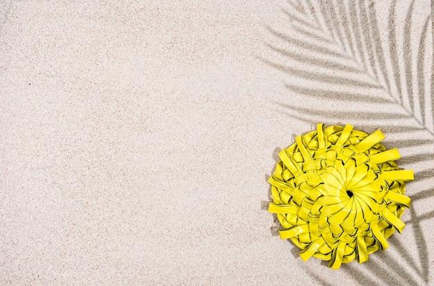 Handgemachter gelber palmenblatthut auf sand mit palmenschatten, draufsicht,
