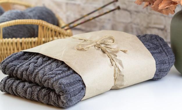 Handgemachter grauer pullover ist in kraftpapier verpackt. handgemachter strickpullover. im hintergrund ein weidenkorb mit stricknadeln.