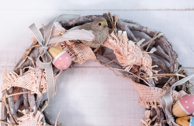 Handgemachter osterkranz aus zweigen und bändern mit süßem vogel und holzeiern