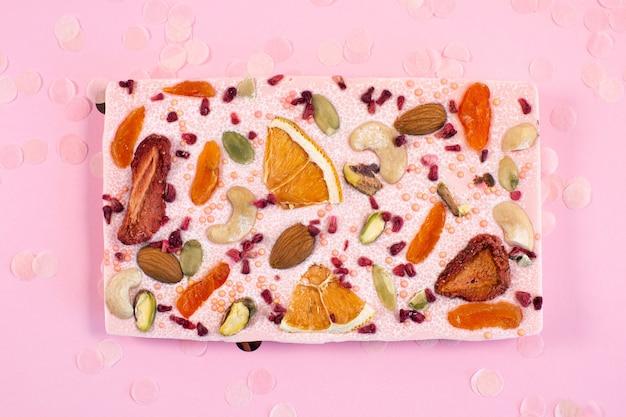 Handgemachter rosa schokoriegel mit getrockneten früchten und nüssen auf fastive rosa hintergrund