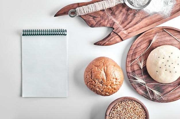 Handgemachter runder brötchenteig in einer holzplatte mit einem rezeptbuch beiseite.