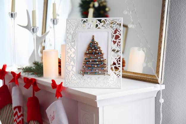Handgemachter weihnachtsbaum im bilderrahmen auf kaminsims