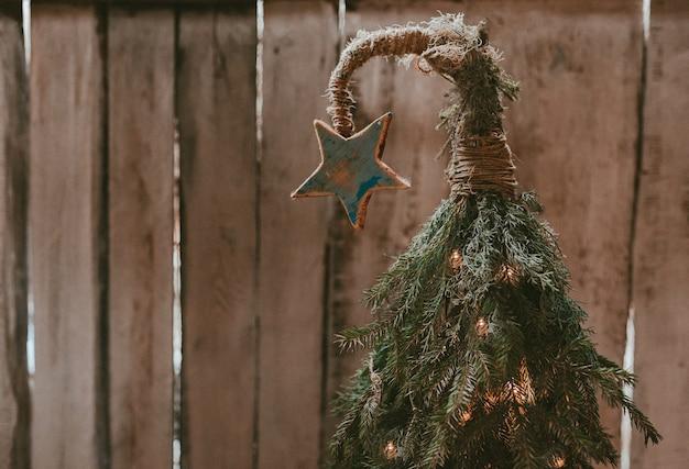 Handgemachter weihnachtsbaum mit einem stern auf einer gebogenen spitze auf einer holzwand. günstiges neues jahr. minimalistischer moderner öko-stil.