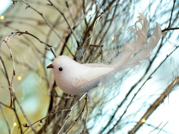 Handgemachter weißer spielzeugvogel auf einem ast