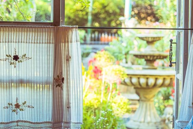 Handgemachter weißer vorhang mit fensteransicht des brunnens und grün vom baumgartenhintergrund
