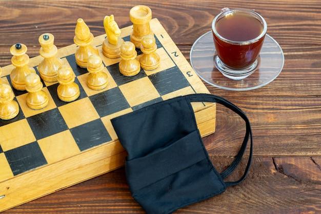 Handgemachtes altes schach auf einem holzbrett. beruf im urlaub und quarantäne. das konzept der isolation.