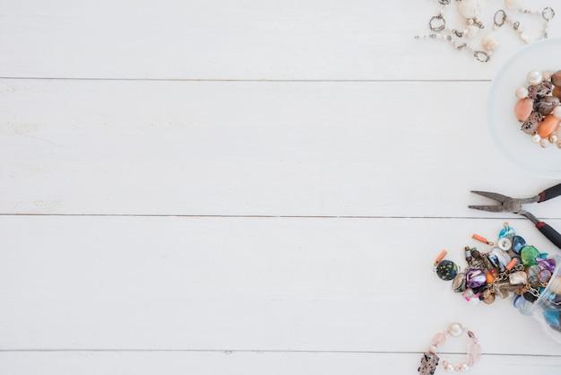 Handgemachtes armband und zangen auf weißem hölzernem schreibtisch