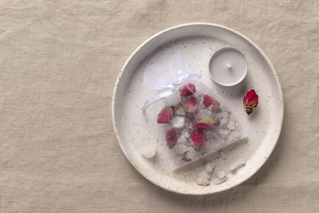 Handgemachtes badesalz mit getrockneten rosen und kräutern im netzbeutel