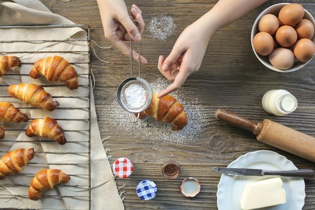 Handgemachtes croissant mit puderzucker auffüllen