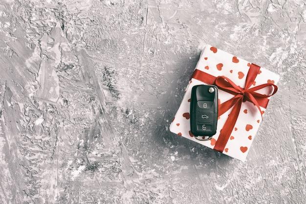 Handgemachtes geschenk des valentinsgrußes oder anderen feiertags im papier mit roten herzen, autoschlüsseln und geschenkbox in der feiertagsverpackung. kastengeschenk auf grauer zementtischplatteansicht mit kopienraum, leerer raum für design