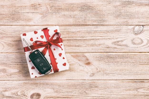 Handgemachtes geschenk des valentinsgrußes oder anderen feiertags im papier mit roten herzen, autoschlüsseln und geschenkbox in der feiertagsverpackung. kastengeschenk auf orange draufsicht des holztischs mit kopienraum, leerer raum für design