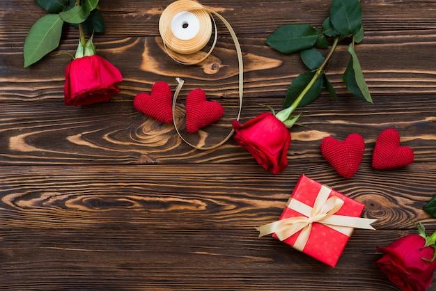 Handgemachtes geschenk des valentinsgrußes oder anderen feiertags mit roten herzen und geschenkbox in der feiertagsverpackung. präsentkartondekoration des geschenks auf draufsicht des holztischs mit kopienraum, leerer raum für design.