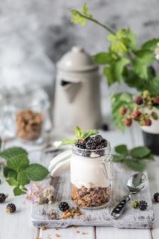 Handgemachtes granola mit weißem natürlichem jogurt mit brombeeren in einem transparenten glasglas, in den blumen und in den blättern auf einem weißen hölzernen hintergrund.