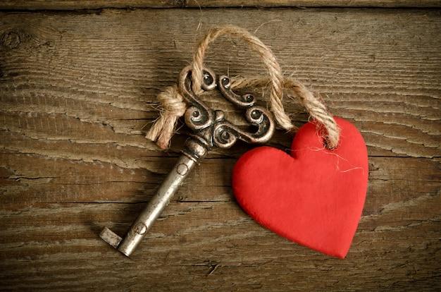 Handgemachtes herz mit schlüssel auf holz
