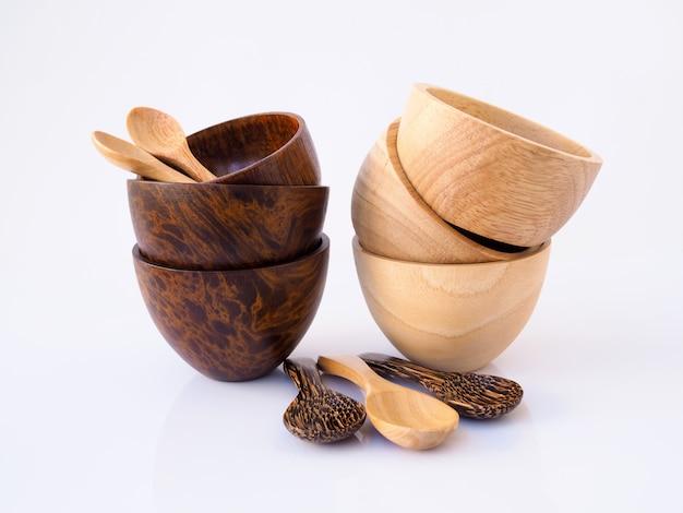 Handgemachtes hölzernes speisendes set mit cup, schüssel und löffel, gerät für das essen getrennt auf weißer oberfläche.