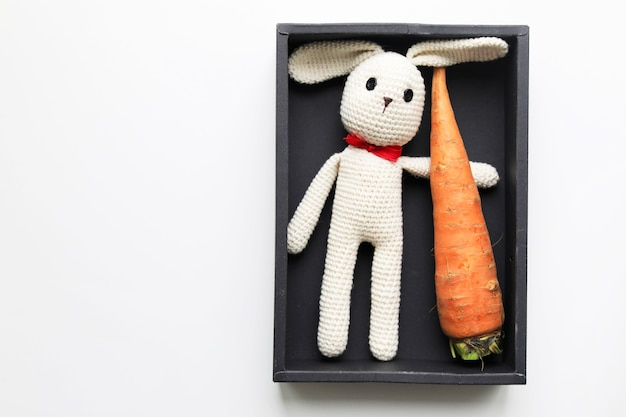 Handgemachtes kinderspielzeug mit gehäkeltem weißem hasen mit einer karotte